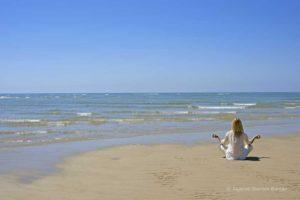 Woman meditating ion Algarve beach